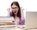 Angry woman sitting at the table with books and laptop